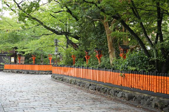 石畳と緑,朱色の名札が鮮やかな祇園の風景